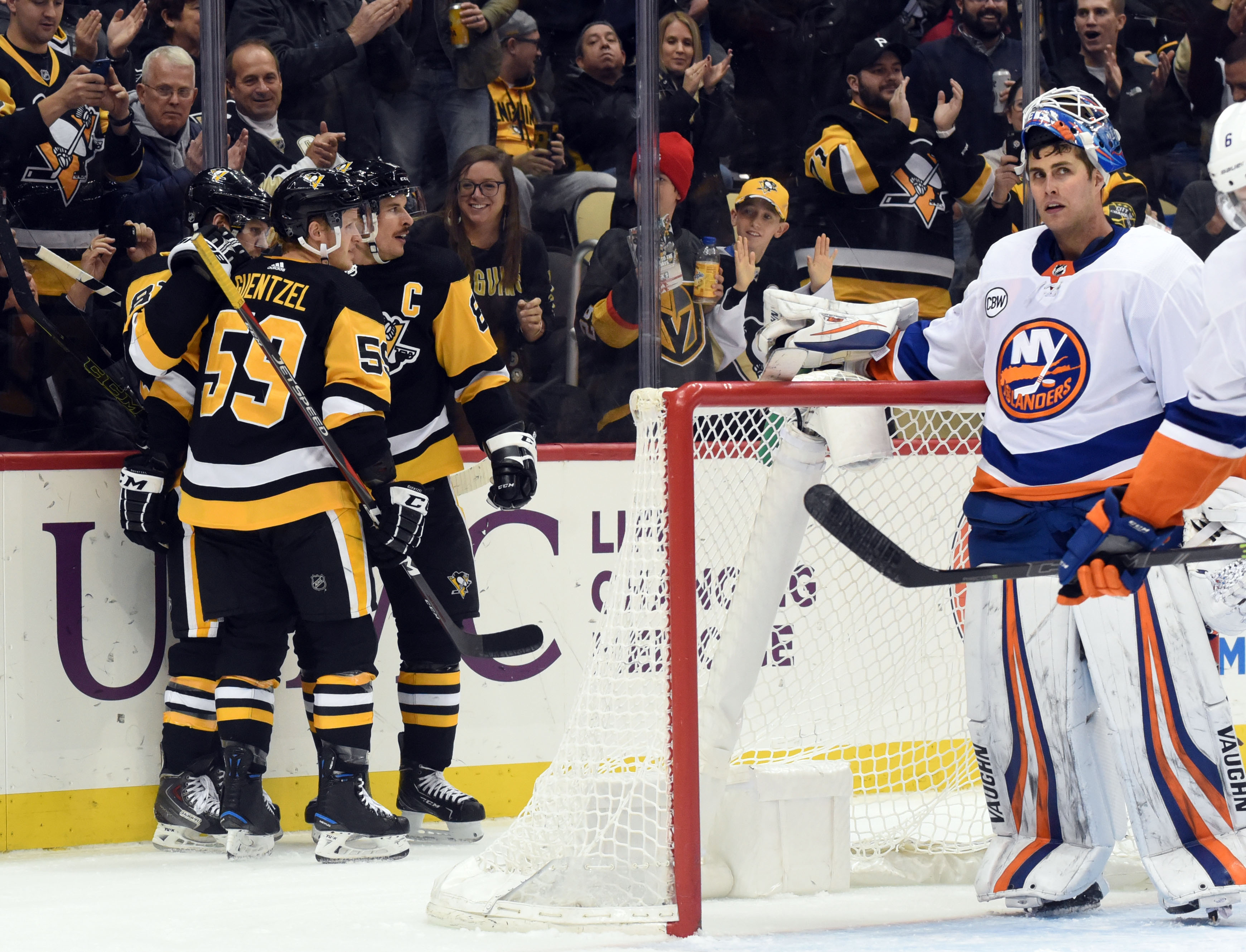 Dec 6, 2018; Pittsburgh, PA, USA; Pittsburgh Penguins winger Phil Kessel (81) celebrates a second period goal with captain Sidney Crosby (87) and winger Jake Guentzel (5) by New York Islanders goalie Thomas Greiss (1) at PPG PAINTS Arena. Mandatory Credit: Philip G. Pavely-USA TODAY Sports