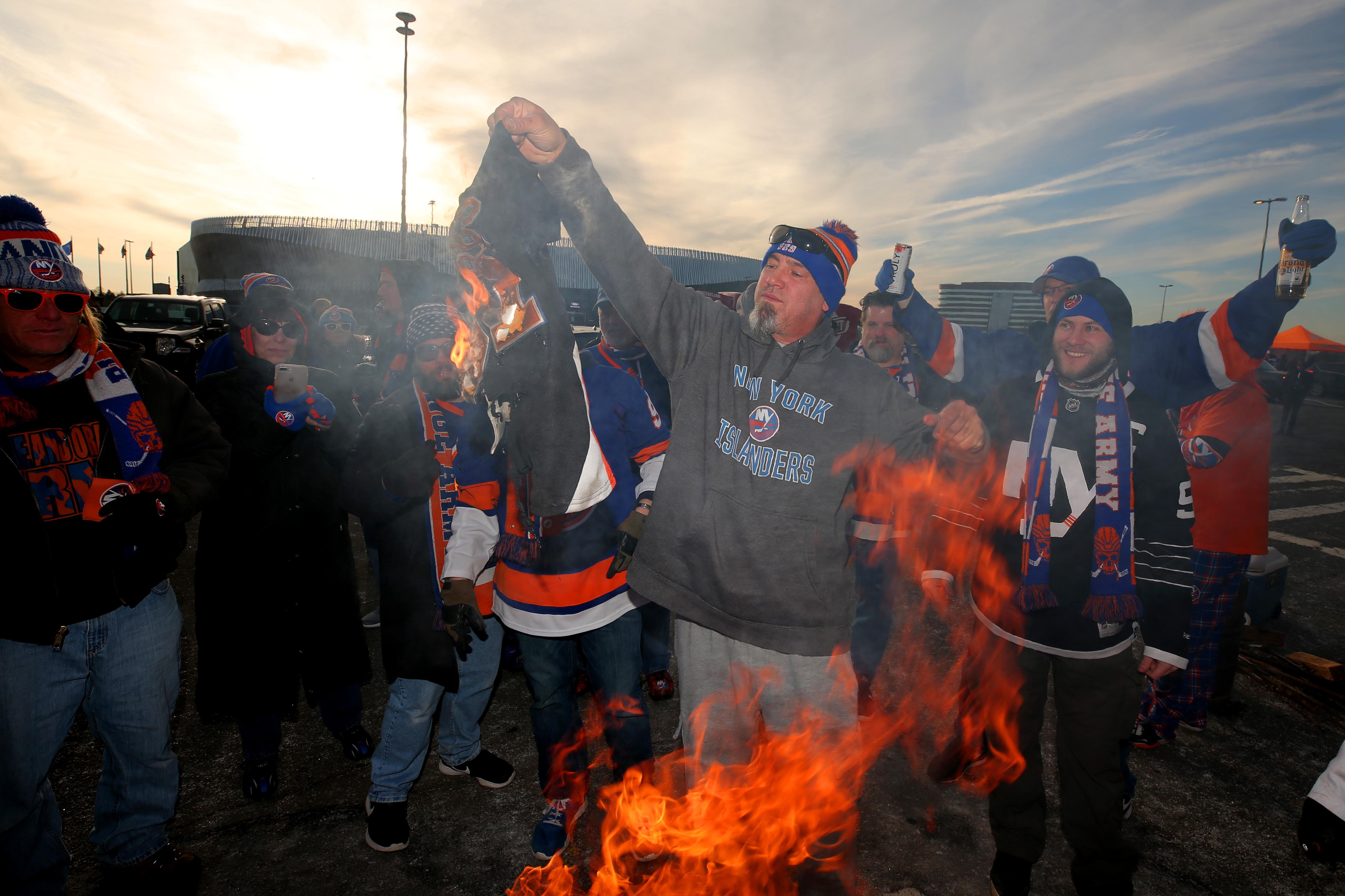 Feb 28, 2019; Brooklyn, NY, USA; New York Islanders fan Craig Richardson of Seaford (center) burns a John Tavares Islanders t-shirt before a game against the Toronto Maple Leafs at the Nassau Veterans Memorial Coliseum. Mandatory Credit: Brad Penner-USA TODAY Sports