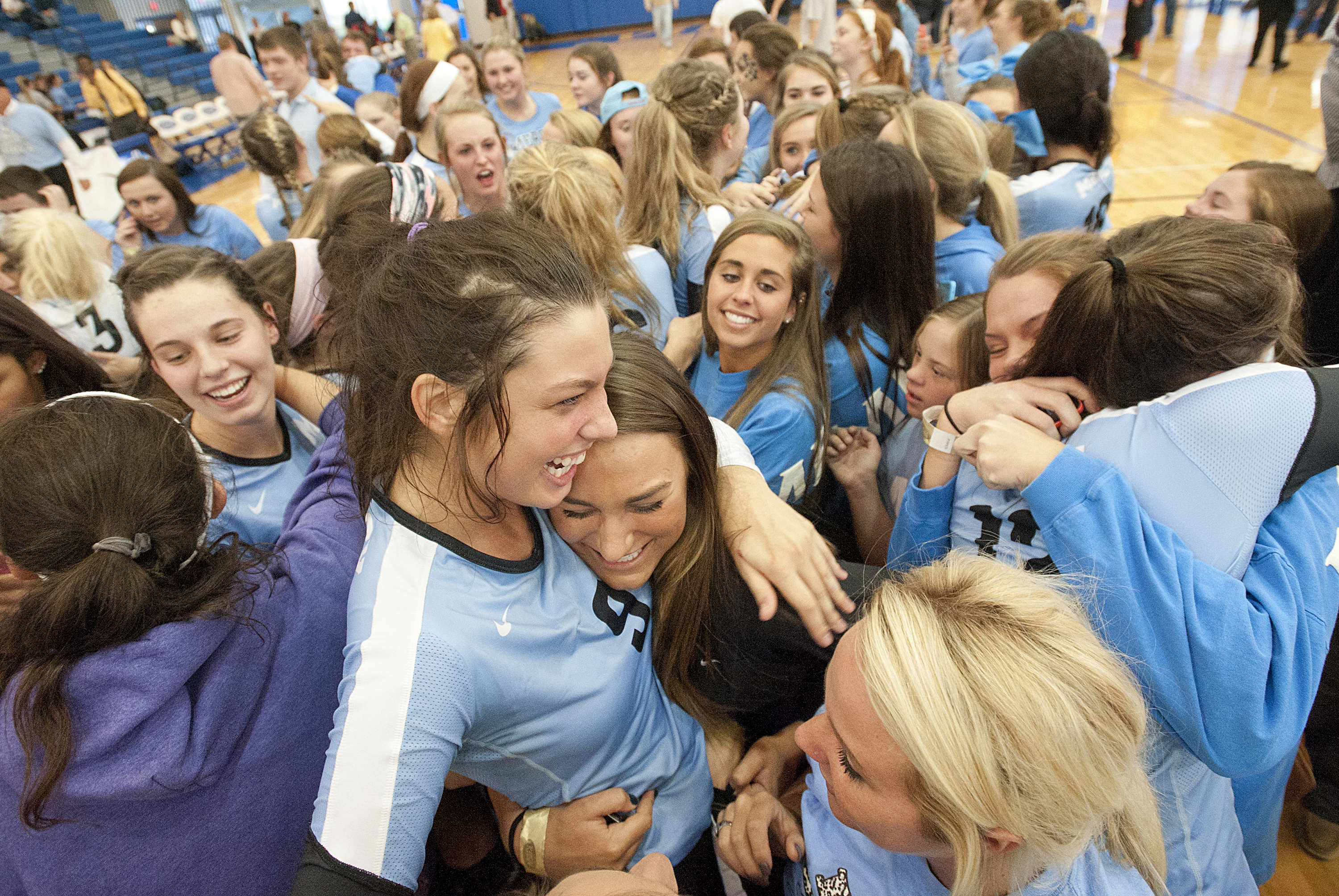 Mercy Academy Jaguars' middle blocker Alexandra Hamrick, center, and her teammates are swarmed with hugging fans, friends and family members moments after Mercy won the state volleyball championship. (By David R. Lutman / Special to The Courier-Journal)