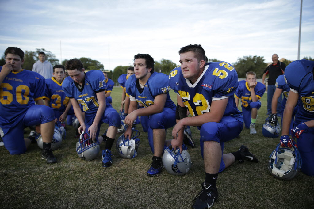 Pahranagat Valley Panthers players listen to their coach after practice in Alamo, Nev. The Panthers, who play eight-man football, have won 75 consecutive games. (AP Photo/John Locher)
