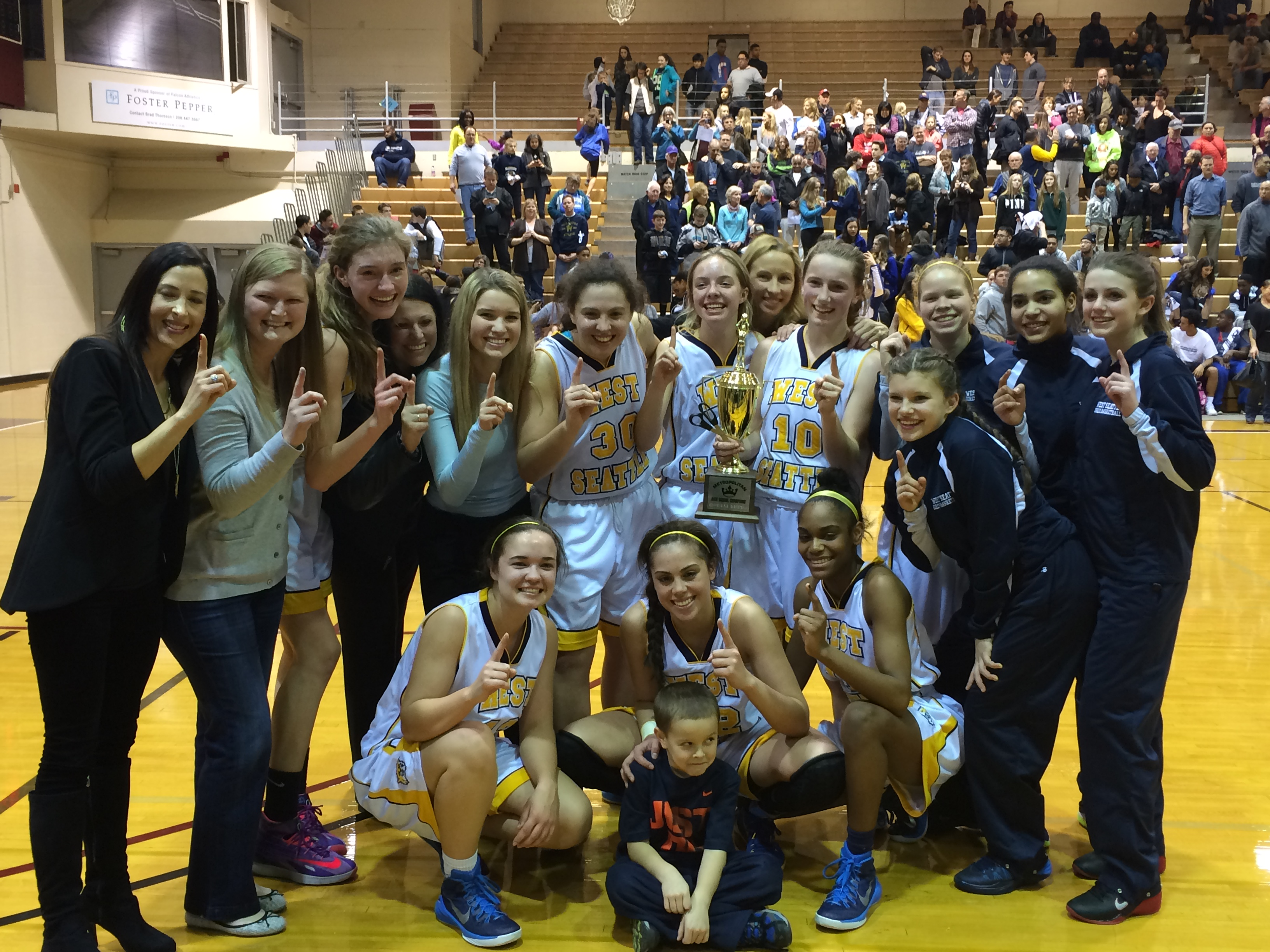 The West Seattle girls basketball team poses with its championship trophy.