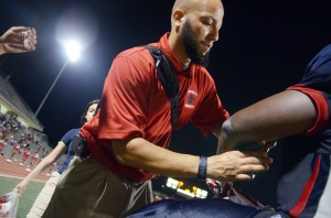 Aaron Ellis, MEd, ATC, LAT, the athletic trainer at Kimball High School in Dallas, Texas, provides medical care for the team during its opening football game of the 2014 season. (Renee Fernandes/National Athletic Trainers' Association)