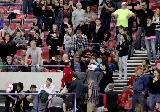Medical personnel care for a man who collapsed during the OSAA high school state wrestling finals at Memorial Coliseum in Portland on Saturday. The man was later identified as Larry Hofenbrel (Photo:  Anna Reed / Statesman Journal)