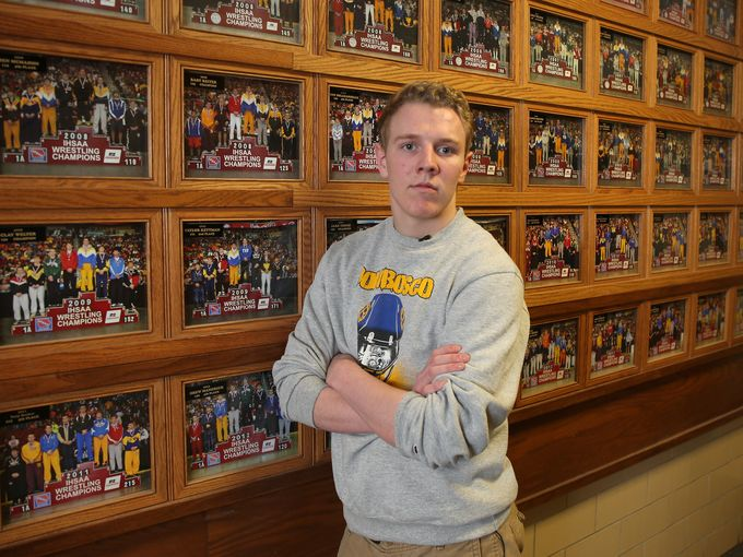Cole Fox, a two-time state wrestling qualifier for Don Bosco High School in Gilbertville, stands in front of a photo wall that commemorates the school's state wrestling placewinners. (Photo: Bryon Houlgrave/The Register)