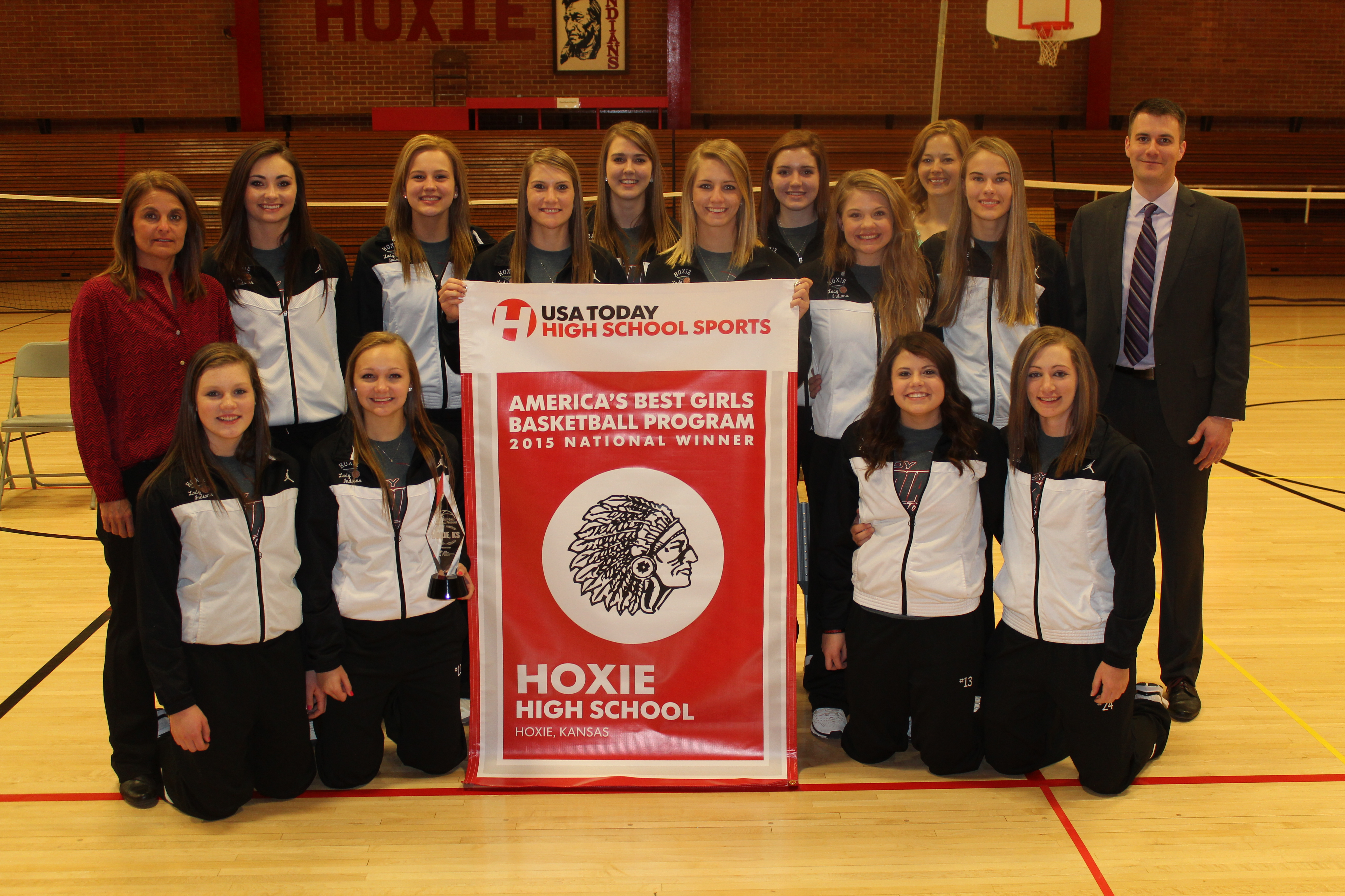 The Hoxie girls basketball team displays its banner for winning the Best Girls Basketball Program contest (Photo: Hoxie High School)