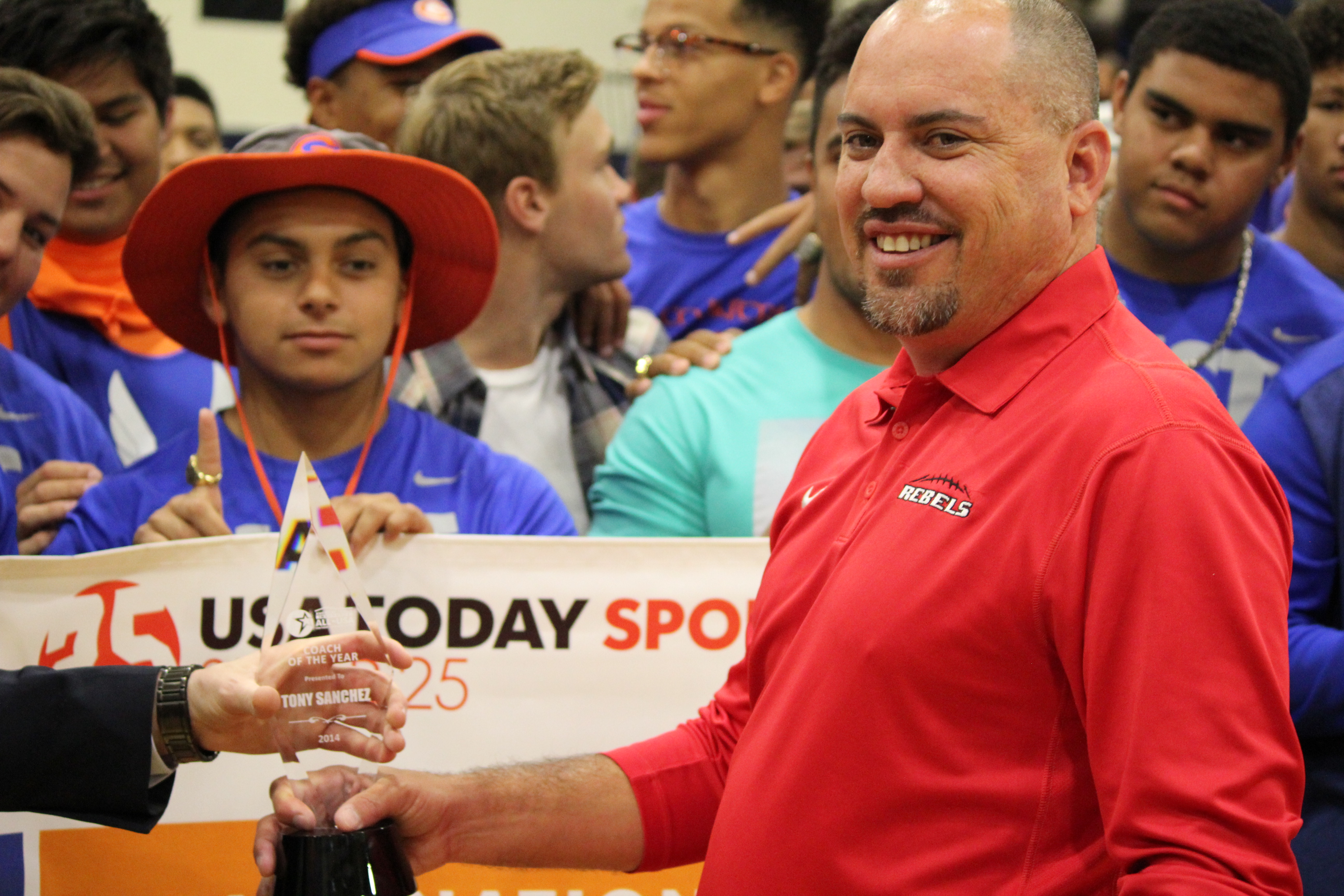 Tony Sanchez accepts the trophy as the American Family Insurance ALL-USA Coach of the Year (Photo: UNLV)