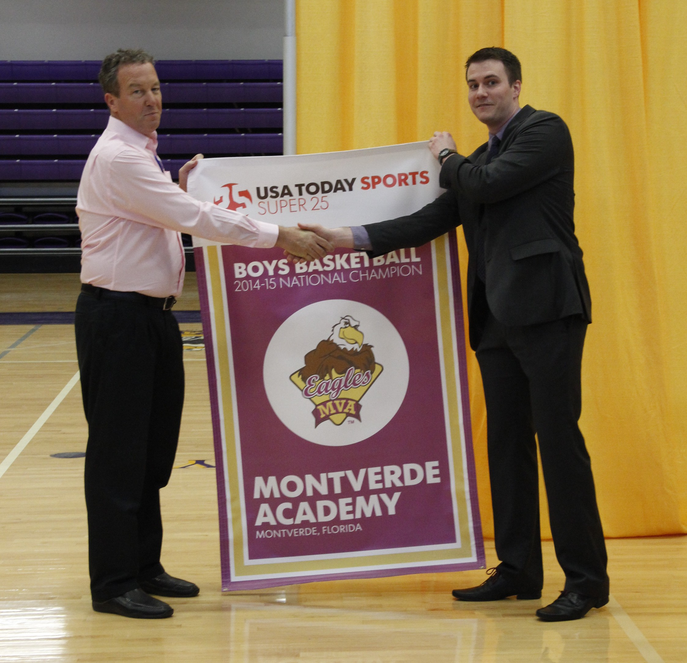 Montverde Academy basketball coach Kevin Boyle (left) accepts the Super 25 national championship banner from Matt Wade of USA TODAY Sports during a ceremony at the school (Photo: Montverde Academy)