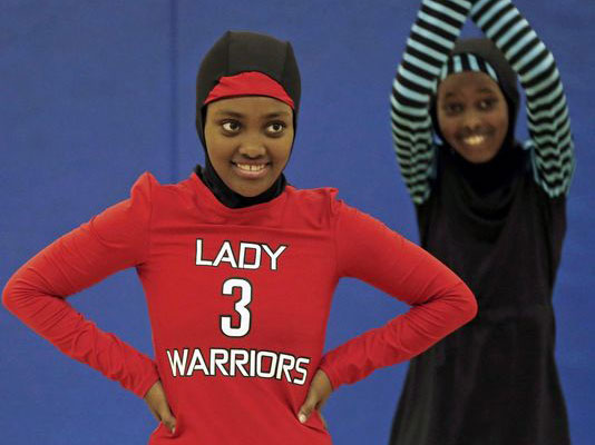 Zubeda Chaffe, left, waits to get back into basketball practice in her new Lady Warriors uniform in Minneapolis. The girls came up with their own culturally sensitive sportswear designs that cover their arms, legs, hair and neck preserving the modesty their religion requires. (Photo: Jim Mone Associated Press)