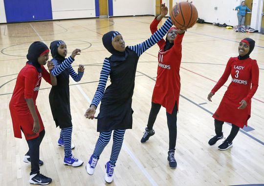 East African Muslim girls practice basketball in their new uniforms in Minneapolis. The culturally sensitive uniforms, designed by the girls, address worries over tripping on a long, flowing dress, or having a loosely wrapped hijab come undone during a crucial play. (Photo: Jim Mone Associated Press)