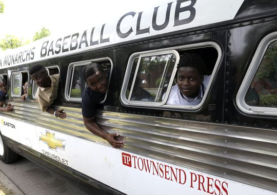 Members of the Anderson Monarchs stick their heads out the windows as they tour in a 1947 vintage bus during their visit to the 16th street Baptist church and Civil Rights Institute on June 24 in Birmingham, Ala. (Photo: Butch Dill, AP)