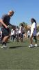 Luken Baker helps a young girl get through drills at the Gatorade Play It Forward Clinic. / Jason Jordan