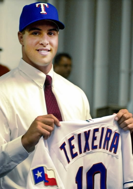 Texas Rangers first round draft pick Mark Teixeira holds his new jersey after the Rangers announced the signing of Teixeira to a four-year, $9.5 million contract in Arlington, Texas, Friday, Aug. 24, 2001. Teixeira will attend the team's Florida Instructional League program at Fort Myers in September. (AP Photo/Bill Janscha)