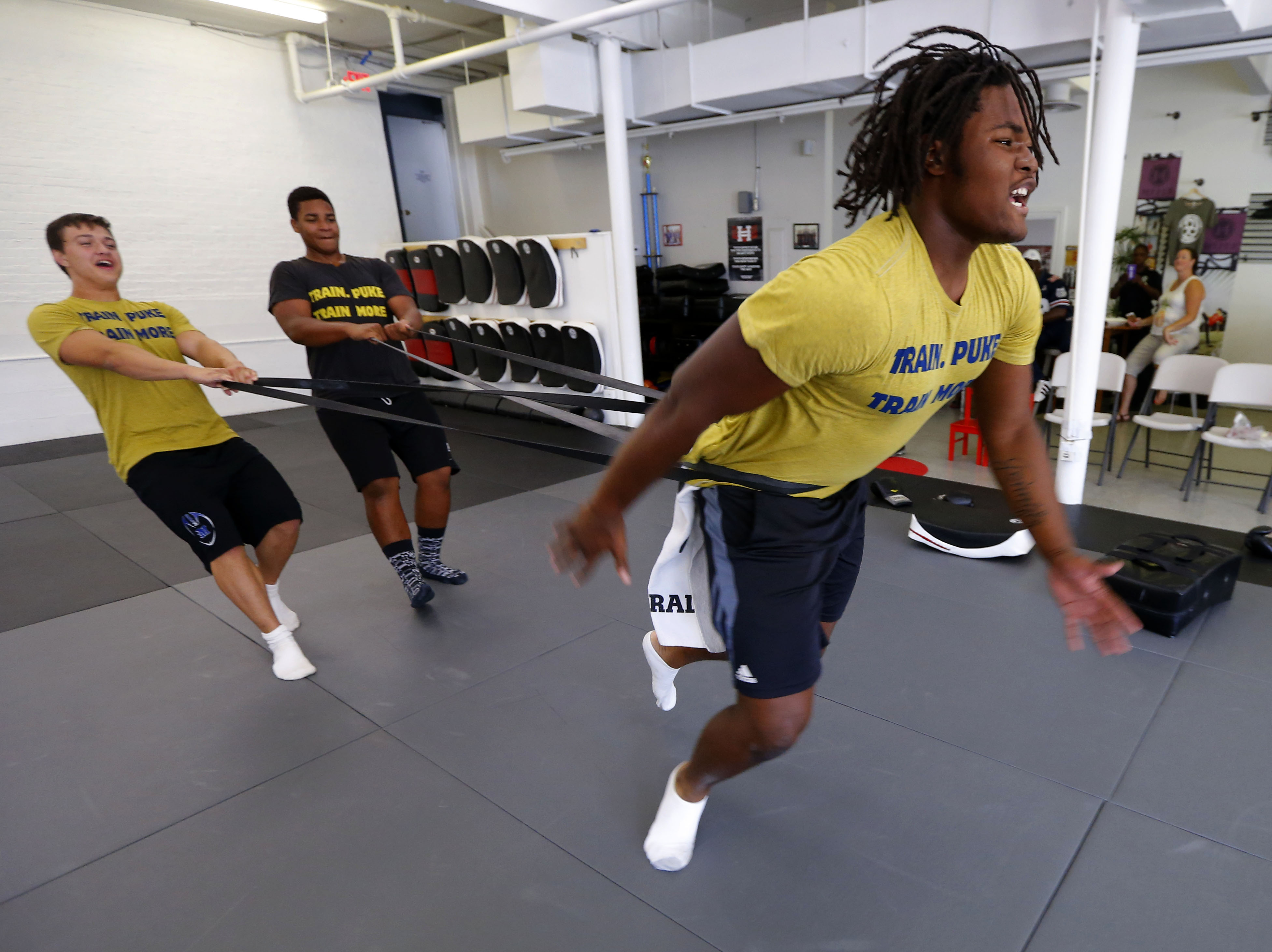 Kevin Ambicki of Middlesex,N.J. and Kevin Knight of North Plainfield, N.J. hold double bands during workout with No. 1 recruit, defensive end Rashan Gary of Paramus Catholic (Paramus, N.J.), and strength trainer, Dwayne Riggins (Photo: Noah K. Murray, USA TODAY Sports)
