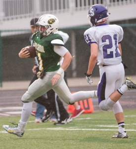 Floyd Central Highlanders quarterback Kyle Peters runs the ball past Seymour Owls defensive back Chris Knight to score the first touchdown of the game. 11 Sept 2015
