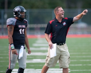 With New Albany Bulldogs quarterback Justin Ricketts watching, Bulldogs head football coach Sean Coultis yells instructions to the defense on the field. 25 Sept 2015