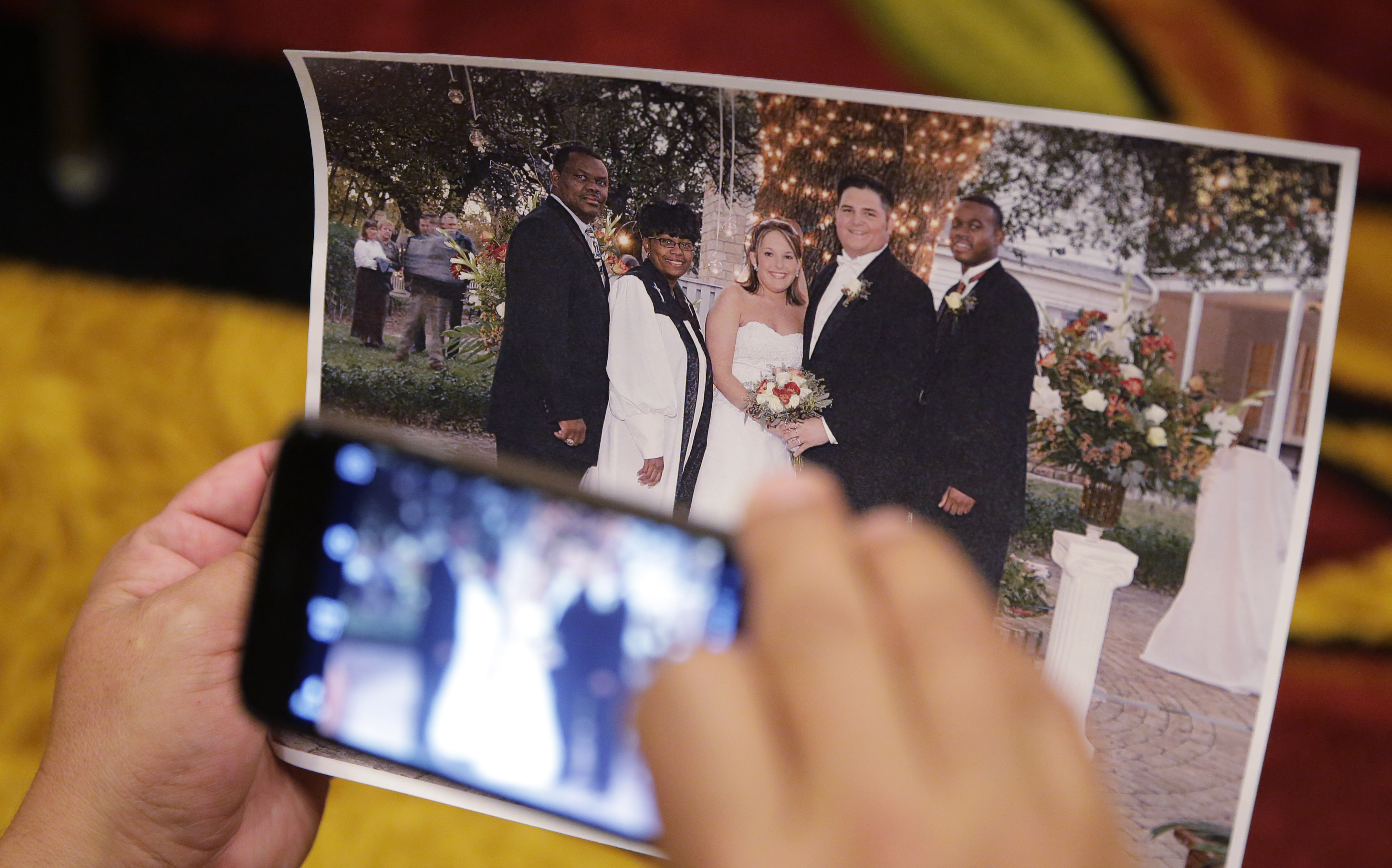 A member of the media copies a photo showing high school referee Robert Watts, second from right, in his wedding (Photo: Eric Gay, AP)