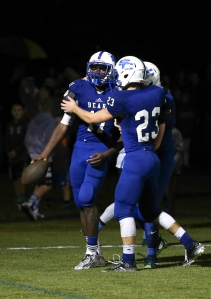 Spencer County's Kadin Smith, left, is greeted by teammates after scoring two touchdowns in less than two-minutes. Sept. 25, 2015