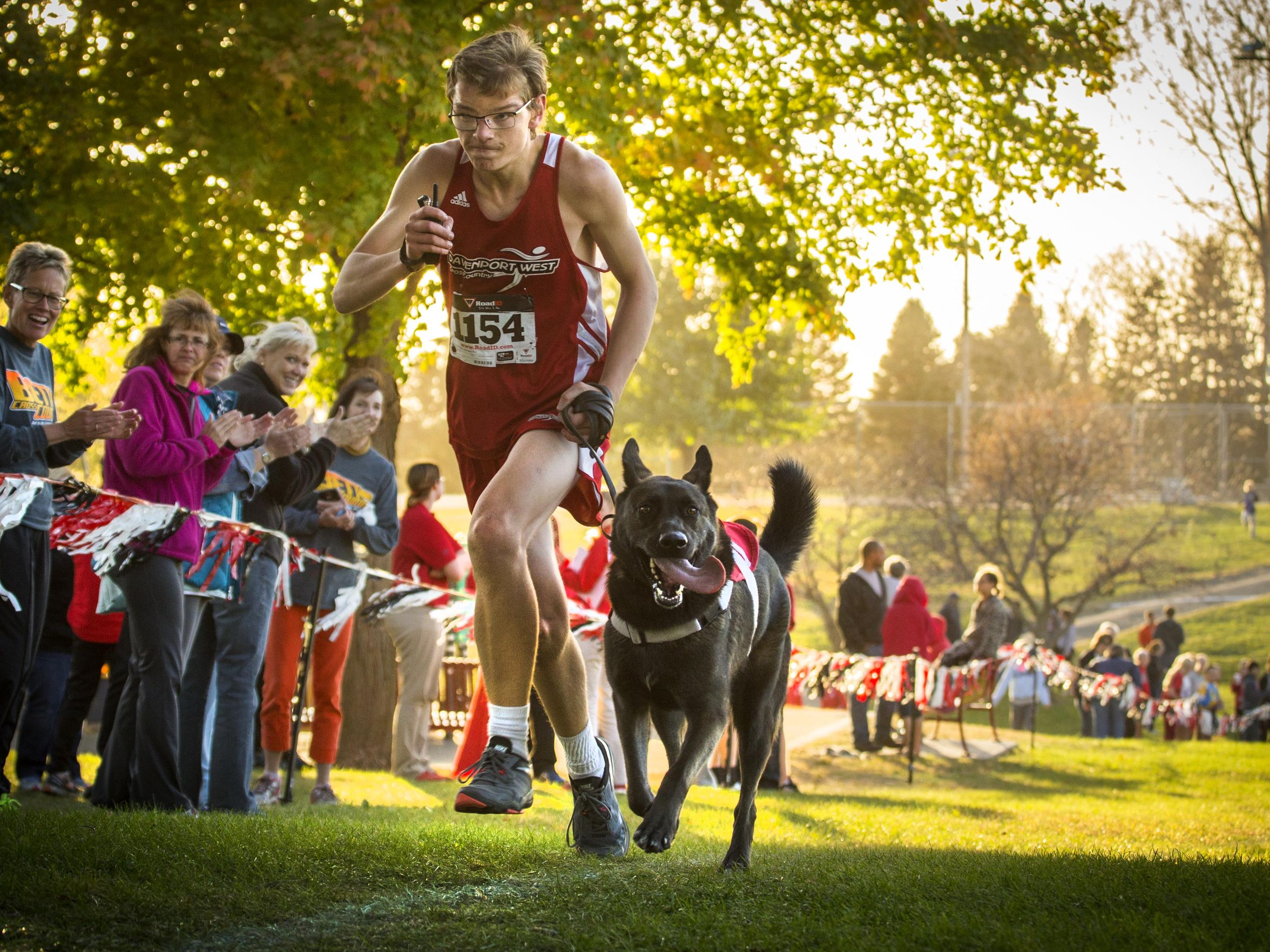 Davenport West's Tyler Gerdt and his German shepherd service dog Hugo nears the finish line during his JV race in Clinton, Iowa, Thursday Oct 15, 2015. Tyler was born with a brain injury, has had 15 surgeries and is autistic. The dog enables him to more effectively and safely run the races, and this has been his first season of running with Hugo. (Photo: Rodney White/The Register)