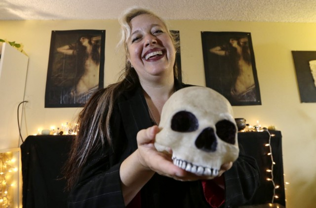 Lilith Starr, chapter head of The Satanic Temple of Seattle, holds a plastic skull while being photographed in her home. (AP Photo/Elaine Thompson)