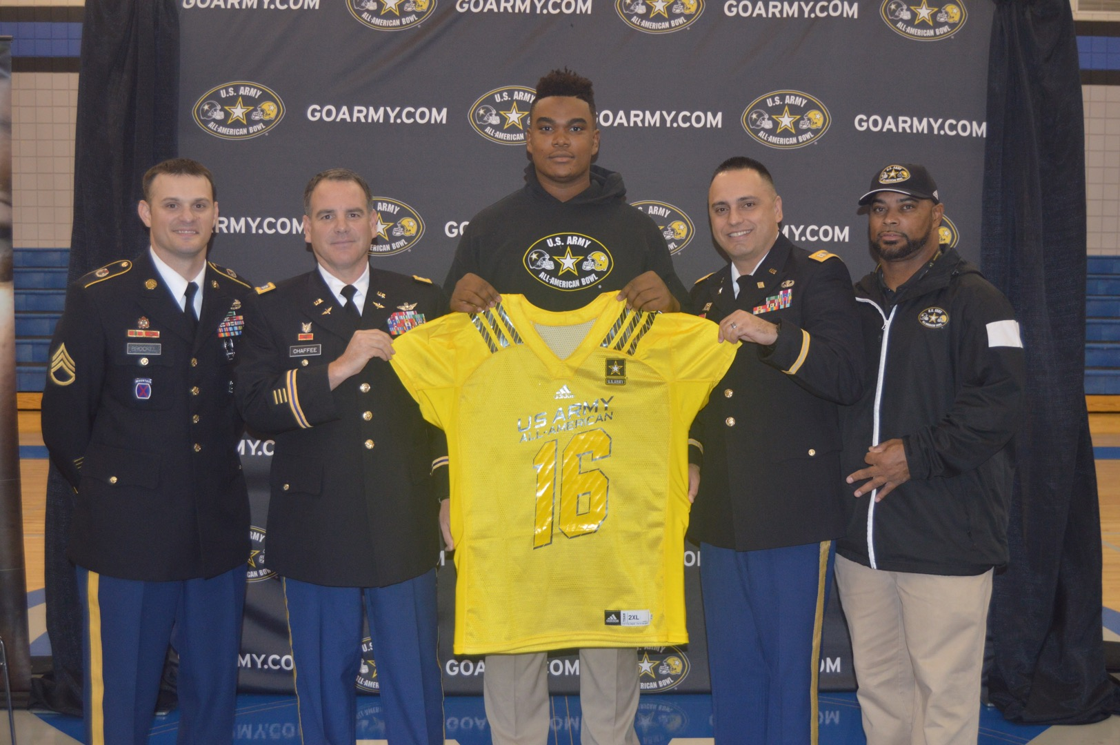 Jordan Elliott receives his Army All-American jersey from (from left): Staff Sergeant Zebedee Brockel, Lieutenant Colonel Chaffee and Captain Rodriguez (Photo: U.S. Army All-American Game)