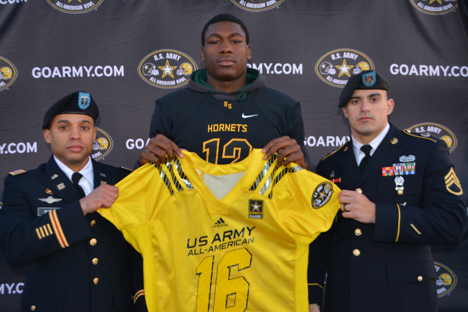 Josh King receivers his Army All-American Bowl jersey from Captain John Butler (left) and Staff Sergeant Yoel Lorenzo.