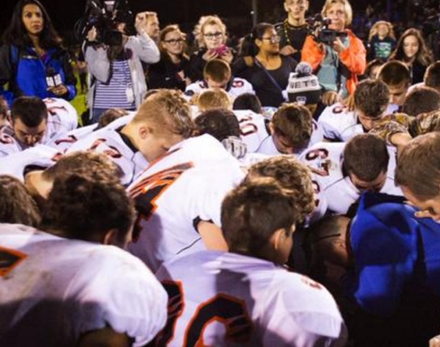 Bremerton coach Joe Kennedy is joined by members of the opposing team for his postgame prayer