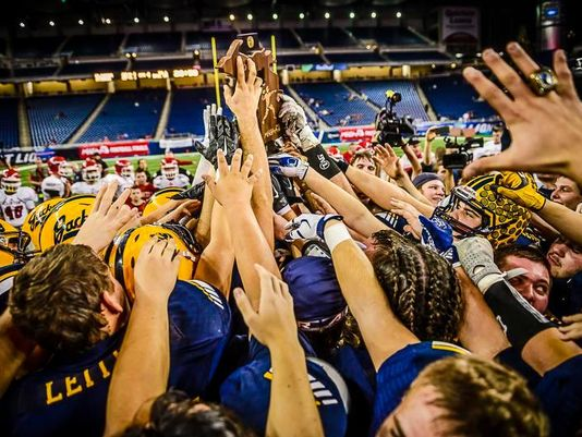 Members of the Ithaca football team lift the Division 6 state championship trophy (Photo: Kevin W. Fowler/For the Lansing State Journal)