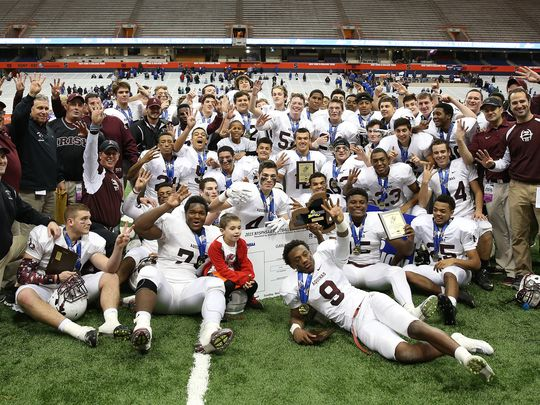 Aquinas players gather for a team photo after beating Saratoga Springs 44-19 to win the State Class AA title. (Photo: Rochester Democrat & Chronicle)