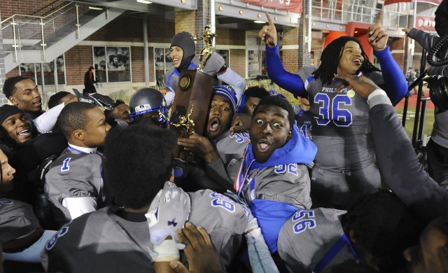 Phillips players celebrate with the trophy after they beat Althoff 51-7 to win the IHSA Class 4A high school championship (Photo: Matt Marton, Associated Press)