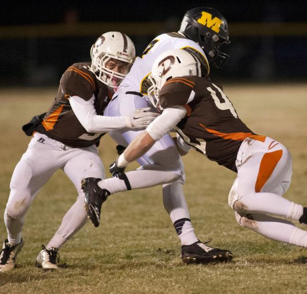 DeSales Colts' defensive back Alec Brothers, left, and  defensive end Ryan Smith, right, stop the run of Murray Tigers' running back Keshon Love in the Class 2-A semi-state final. 28 November 2014