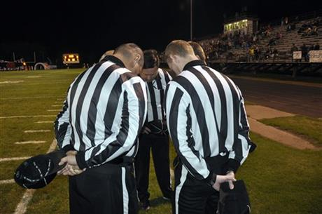 Referee Greg Knight, center, leans in for a pre-game prayer with other officials before a high school football game in Gentry, Ark. Sports officials across the country are facing increasing scrutiny, with many taking out insurance in case they are attacked by fans or coaches. (Photo: Kurt Voigt, AP)