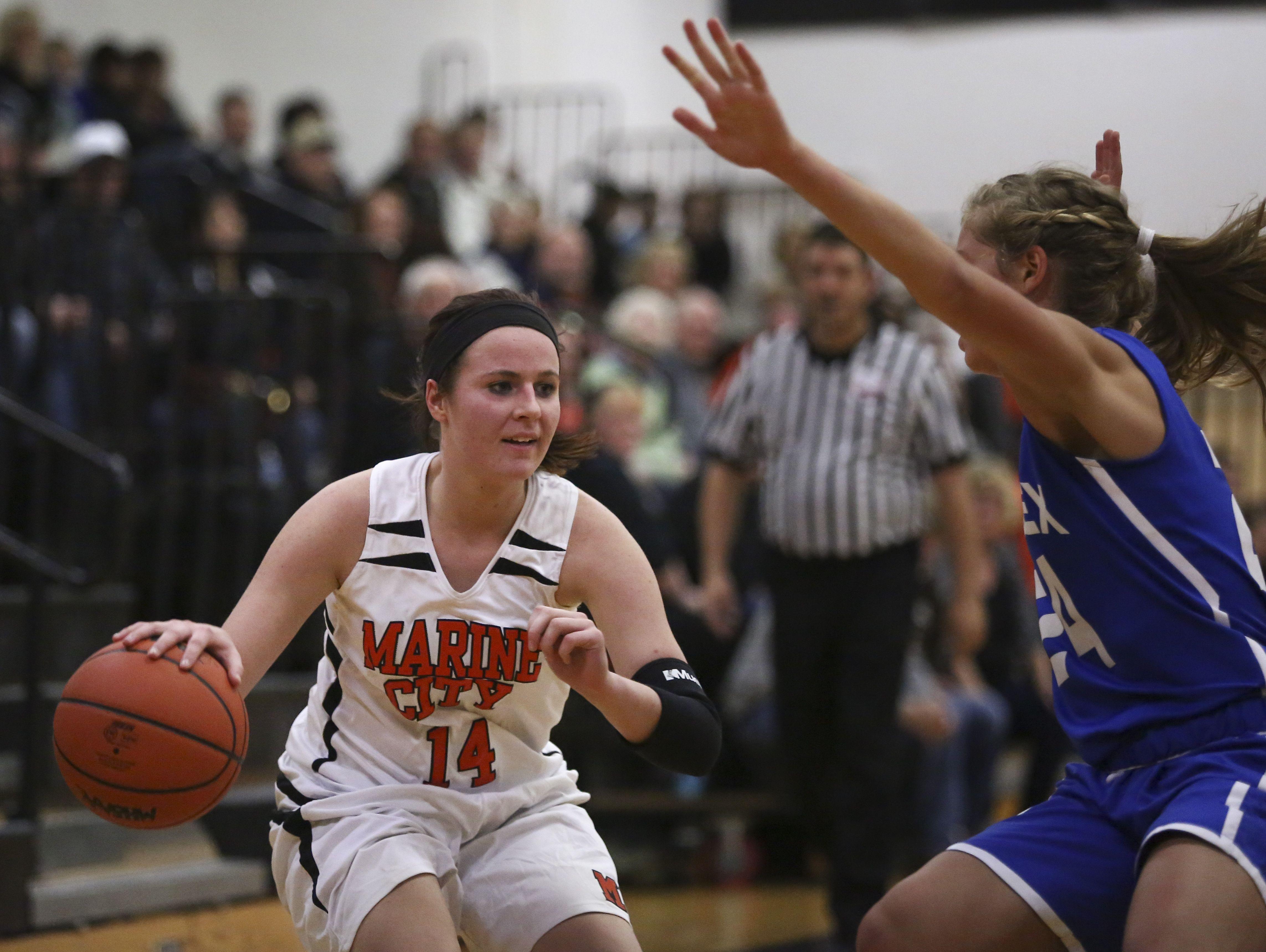 Marine City's Karyssa Austin drives the ball down court as Cros-Lex's Calli Townsend puts on pressure during a basketball game Tuesday, December 1, 2015 at Marine City High School.