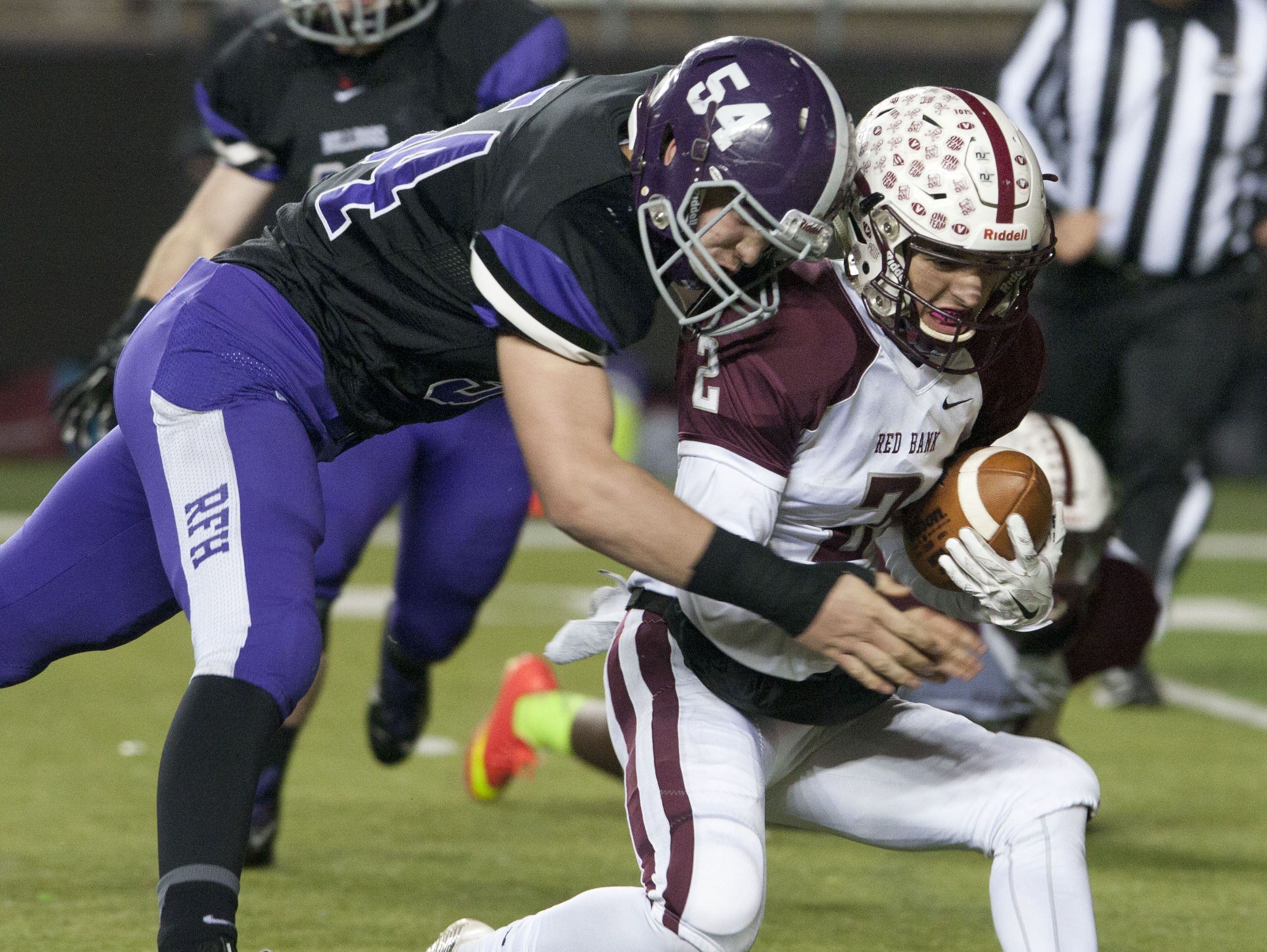 Red Bank Regional quarterback Jack Navitsky is sacked by Rumson's Chase Pfang (54) in Saturday's Central Group III final.