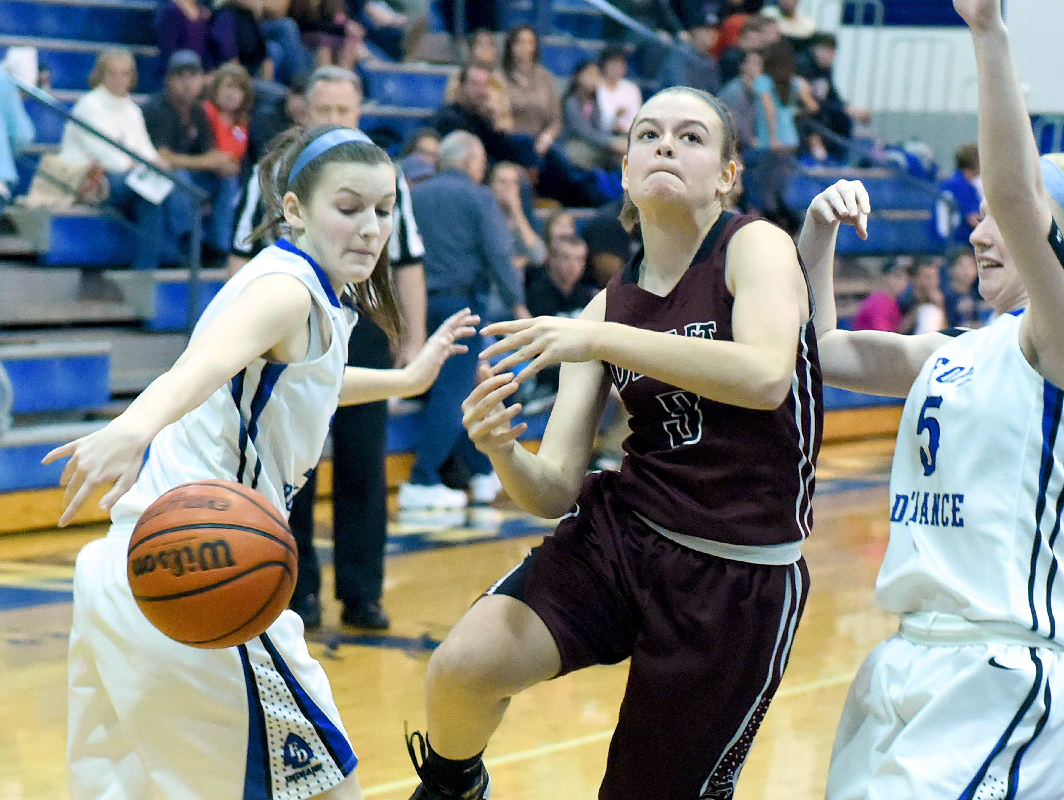 Stuarts Draft's Rachel Sauder tries to slip between Fort Defiance's Erin Henderson and Emily Humphries but Henderson strips the bats the ball away from her as she tried to reach the basket during a basketball game played in Fort Defiance on Friday, Dec. 11, 2015.