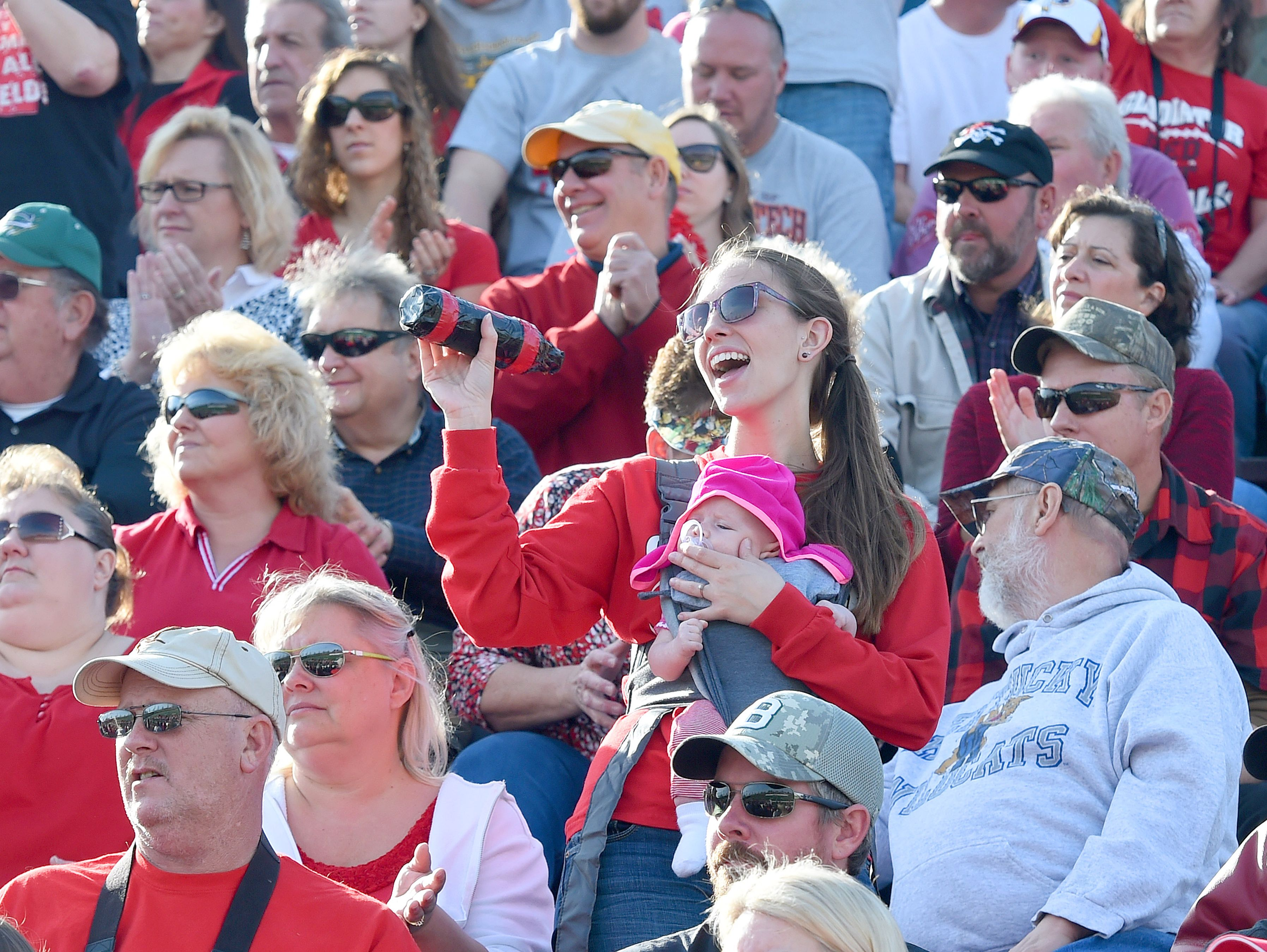 A Riverheads' fan has a baby strapped to her front as she uses a homemade noise maker during the Group 1A football championship in Salem on Saturday, Dec. 12, 2015. Riverheads lost to Galax 7-6.