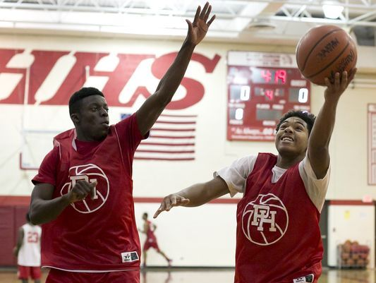 Port Huron senior Damion Farrior takes a layup in front of sophomore Dwight Porter during practice Thursday, December 3, 2015 at Port Huron High School.