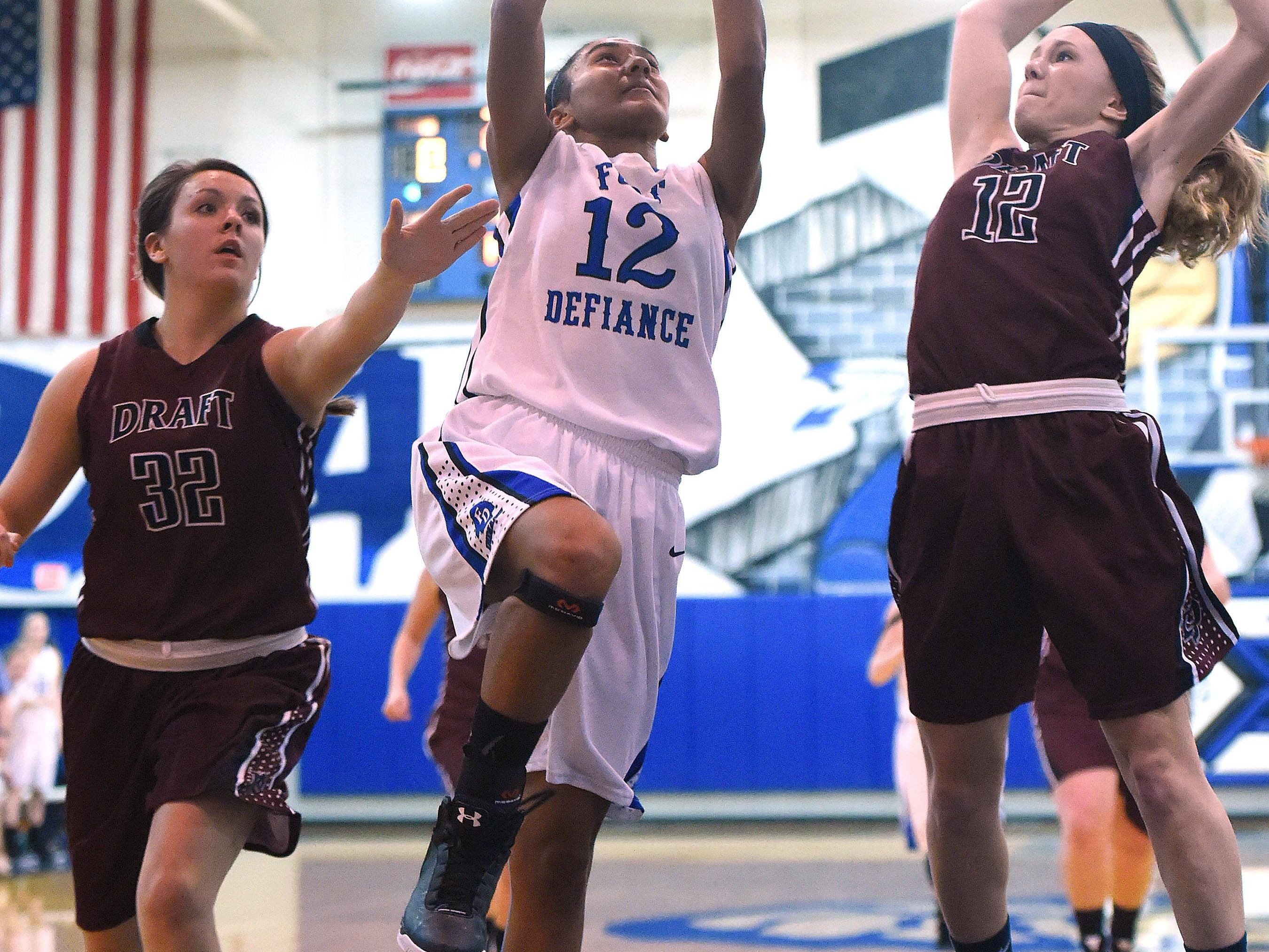Fort Defiance's Tiffany Taylor takes the ball up as Stuarts Draft's Bailey Turner and Deborah Black guard during a basketball game played in Fort Defiance on Friday, Dec. 11, 2015.