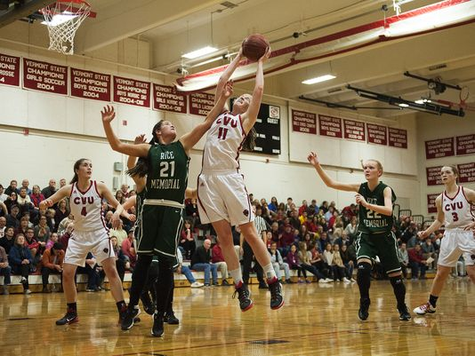 CVU's Laurel Jaunich (11) leaps over Rice's Rachel Chicoine to grab the rebound during the girls basketball game between the Rice Green Knights and the Champlain Valley Union Redhawks on Monday night. (Photo: Brian Jenkins, Burlington Free Press)