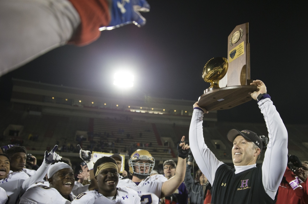 December 5, 2015 -- Bowling Green, Ky. -- Louisville's Male High School takes on Lexington's Lafayette High School in the State Class 6A High School Championship game on Saturday, Dec. 5, 2015 at LT Smith Stadium in Bowling Green, Ky. Male won the game 41 - 14. Male's head coach Chris Wolfe presents the State Championship Class 6A trophy to his team. (Photo by Tim Broekema)