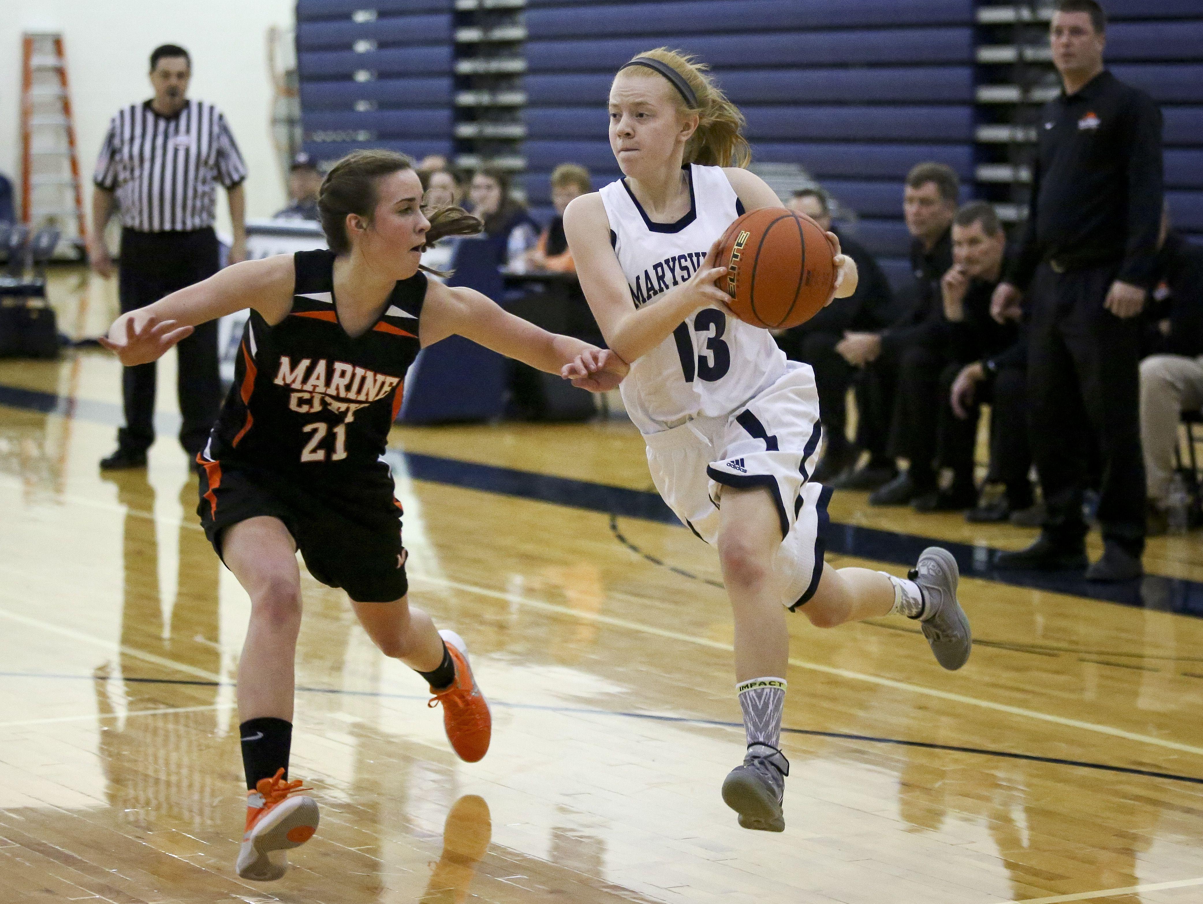 Marysville junior Kiara Kelley drives the ball past Marine City sophomore Stephanie Abraham during a basketball game Friday, Jan. 8, 2016 at Marysville High School.