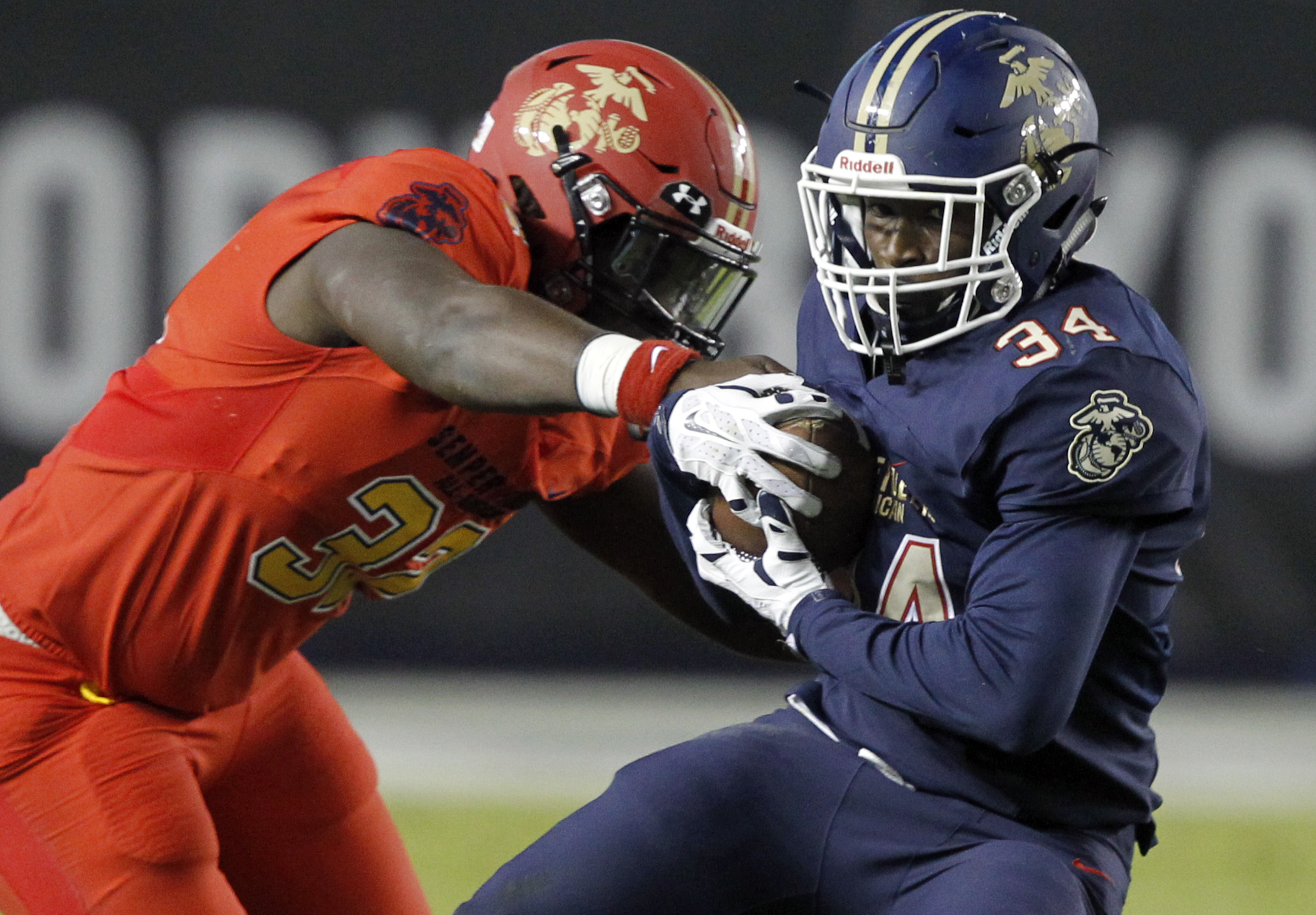 West defensive end Isaiah Chambers, left, gets his hand on the ball, as East running back Amir Rasul runs for a first down Photo: (Alex Gallardo, Associated Press)