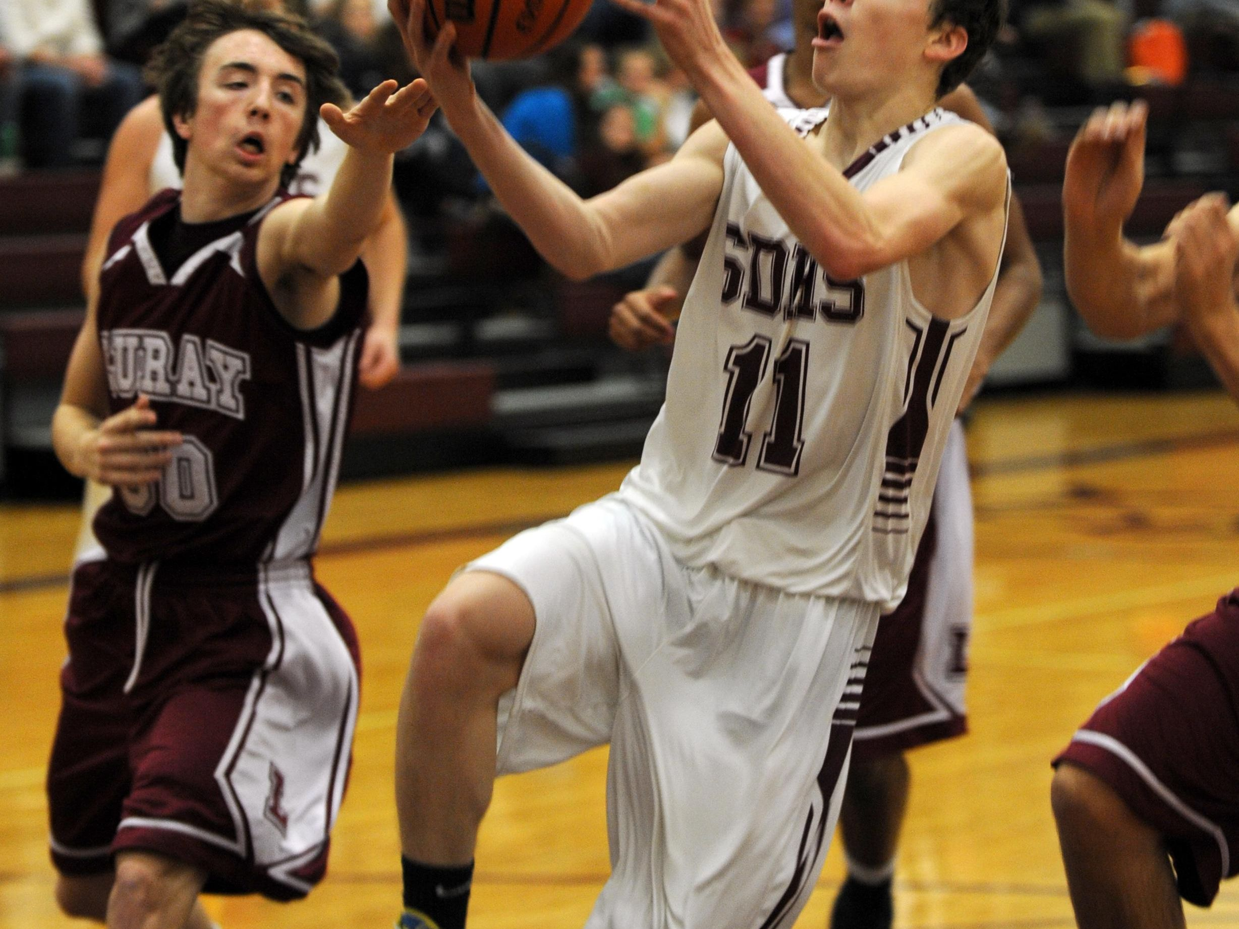 Stuarts Draft's #11, Evan Burgener drives to the basket past Luray's #00, Trea Atkins at Stuart Draft High School during their boys basketball game Monday, Jan. 11, 2016