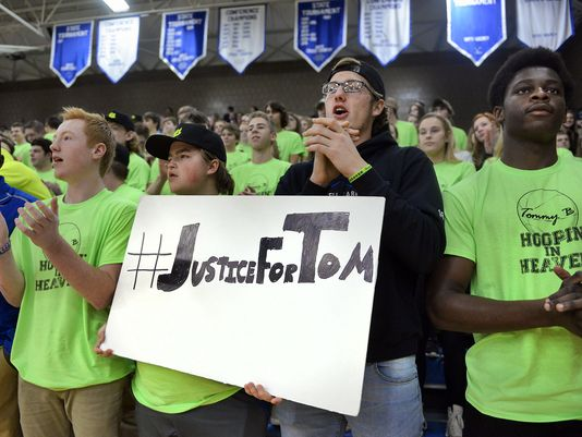 """Sartell fans hold a sign calling for justice in Tom Bearson's murder case Friday, Jan. 8 during the """"Hoopin' for Tommy B"""" tribute and basketball game between Sartell and Rocori at Sartell High School. (Photo: Kimm Anderson, St. Cloud Times)"""