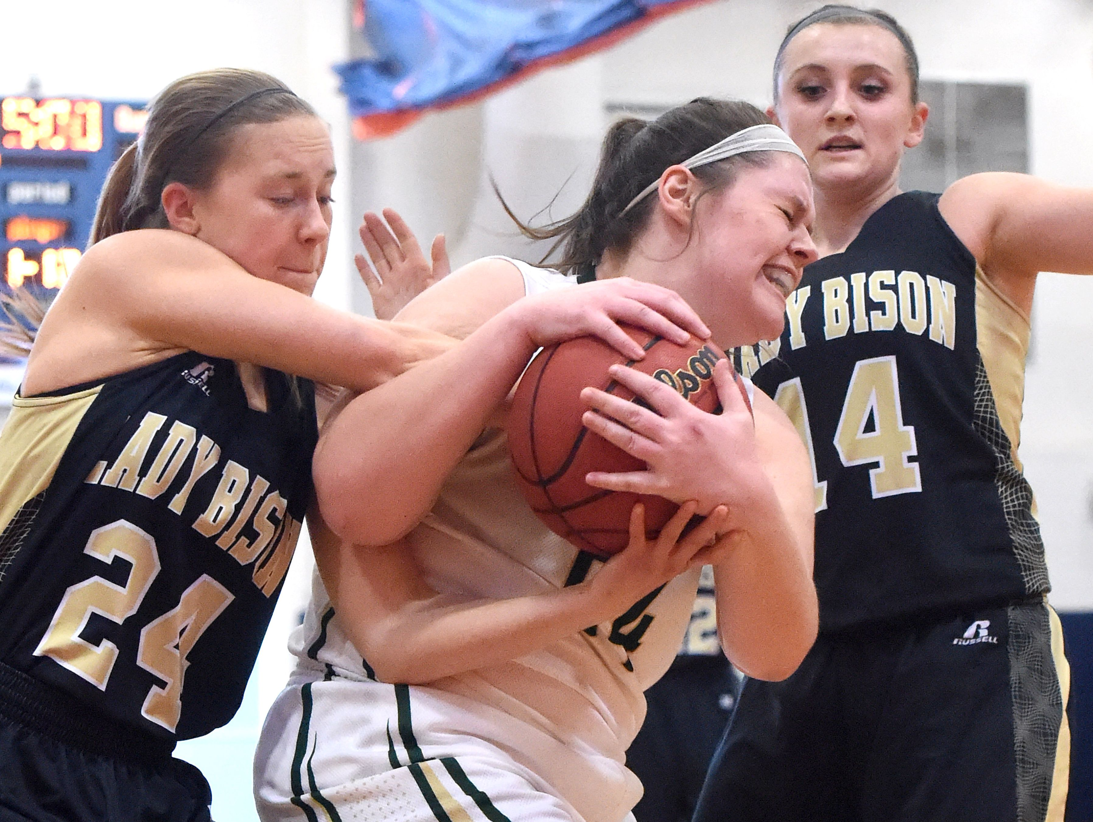 Wilson Memorial's Jordan Sondrol (center) fights to hold onto the ball as Buffalp Gap's Shelby Stenzel tries to strip it from her while Gap's Marybeth Strickler guards during the Region 2A East girls basketball championship played in Orange on Saturday, Feb. 27, 2016.