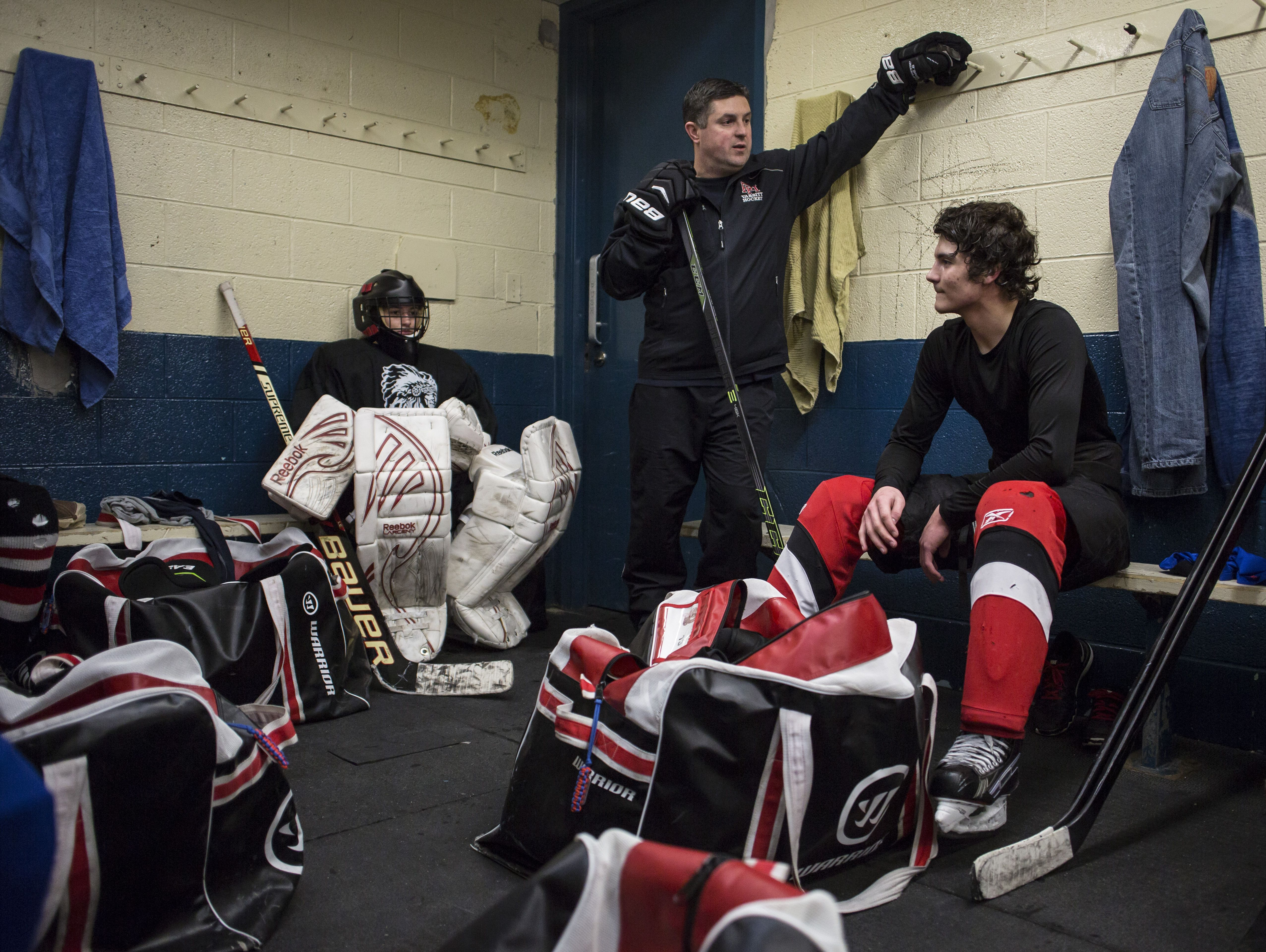 Port Huron goalie Ally Fetterly, left, listens as head coach Ben Poink speaks with players in the locker room during a practice at McMorran Arena in Port Huron.