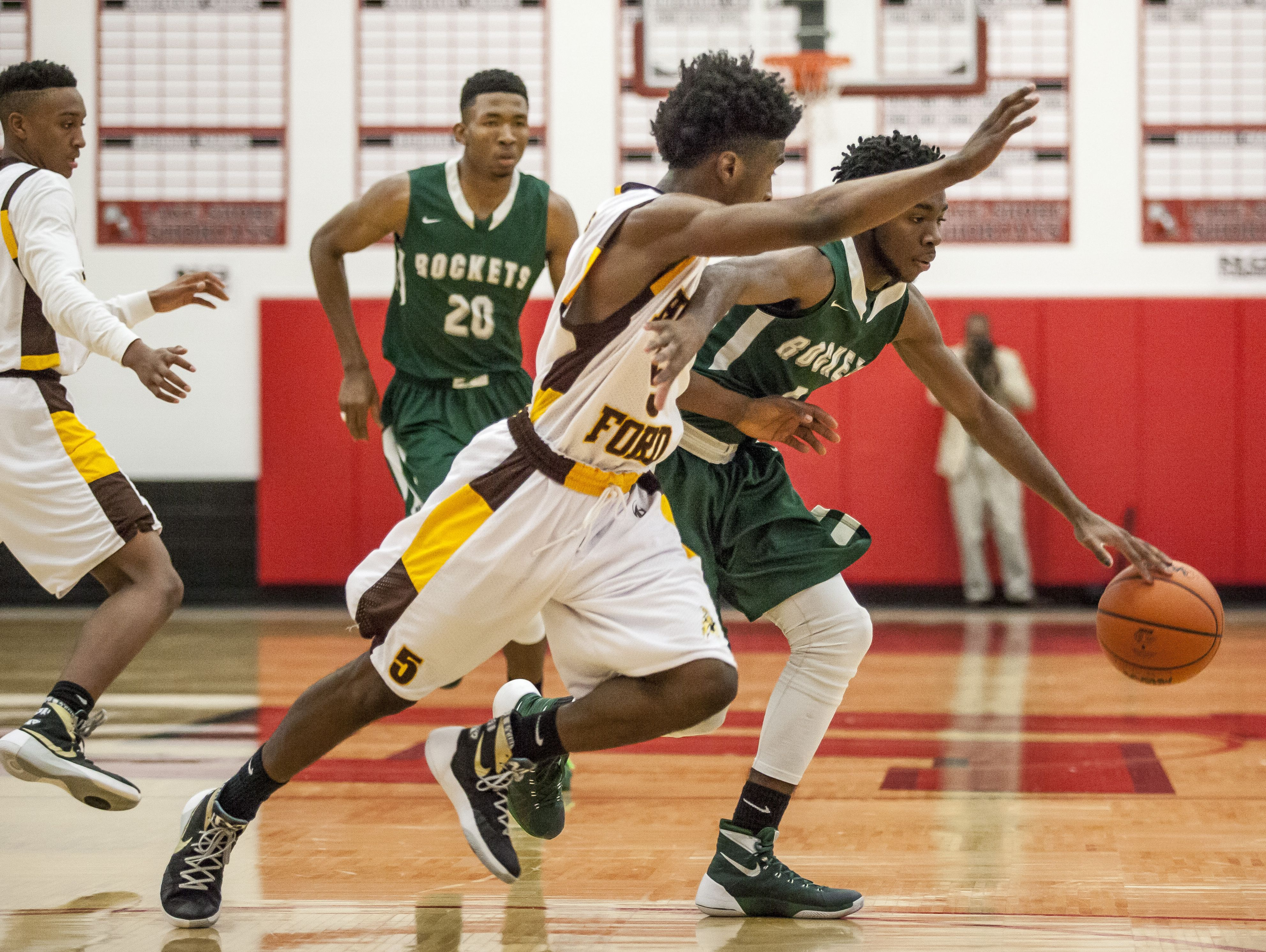 New Haven senior Alante Stevens tries to get past Detroit Henry Ford senior James Towns during a quarterfinal basketball game Tuesday, March 22, 2016 at Lakeshore High School in St. Clair Shores.