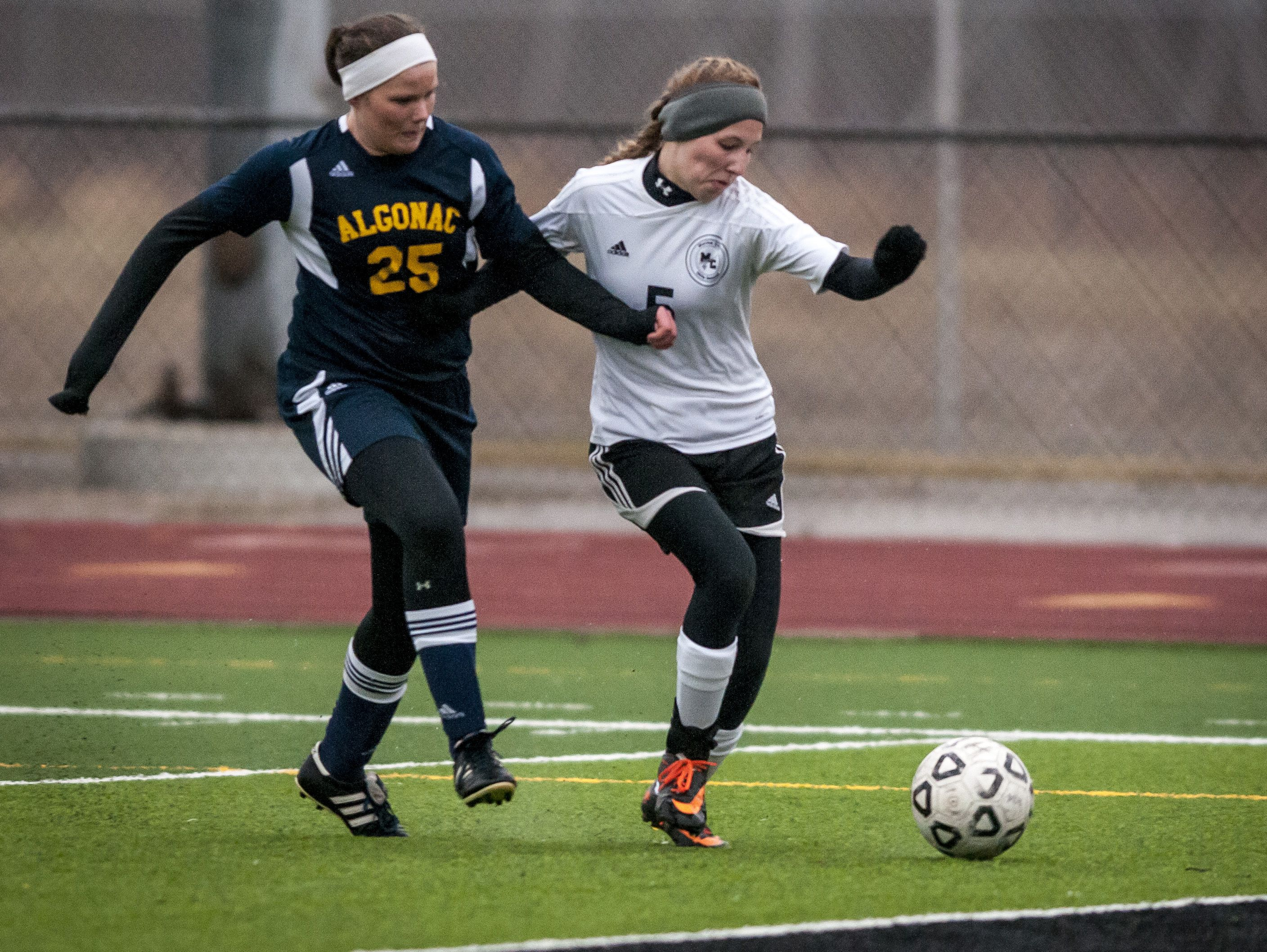Algonac sophomore Madisyn Wilson puts pressure on Marine City junior Emilie Andrews during a soccer game Wednesday, March 23, 2016 at East China Stadium.