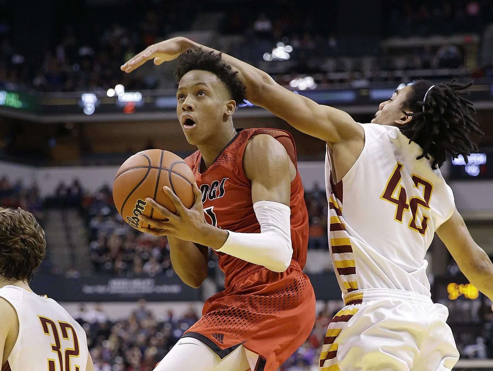 New Albany Bulldogs Romeo Langford (1) drives by McCutcheon Mavericks Billy Loft (42) in the second half of the IHSAA 4A Boys Basketball State Final game Saturday, Mar 26, 2016, evening at Bankers Life Fieldhouse. The New Albany Bulldogs defeated the McCutcheon Mavericks 62-59.