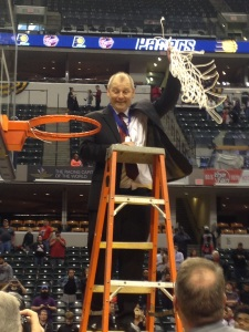 New Albany coach Jim Shannon cuts the net after the Bulldogs' win Saturday in Indianapolis. Photo b y Kenzie Winstead/The Courier-Journal