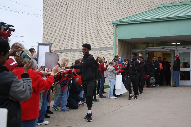 Bulldog Mike Maxwell leads the New Albany team from to the bus Friday morning, passing by a gantlet of fans. (By Jenna Eseray, Special to The CJ)